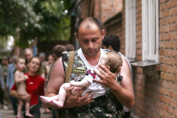 2.) A Russian police office carries a baby that was rescued from a school occupied by militants in the town of Beslan in 2004.