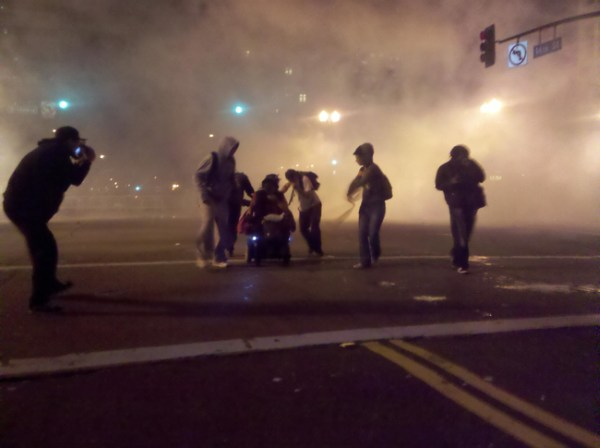 4.) Protestors in Oakland, California, help a woman in a wheelchair get away from teargas.