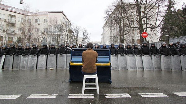 13.) A man plays the piano for riot police in Kiev, Ukraine in 2013.