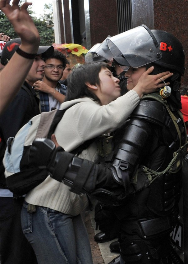 11.) A student protestor in Bogotá, Colombia tries to kiss a riot police officer.