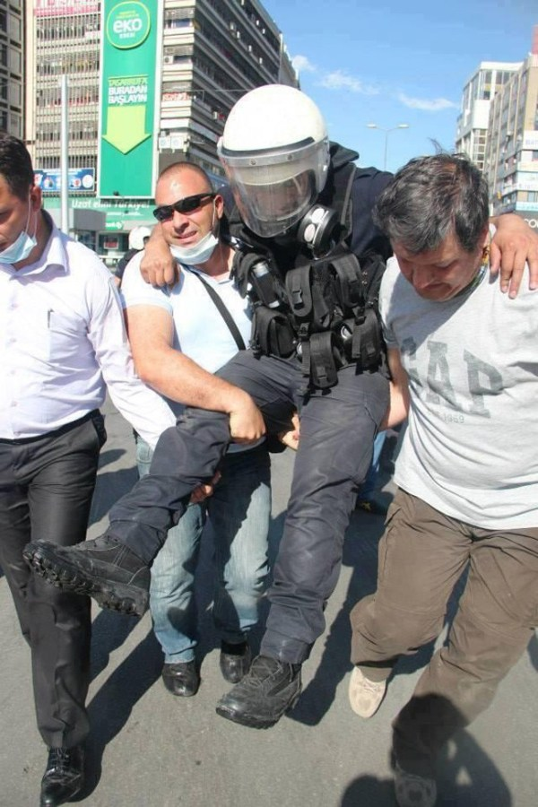 18.) Protestors carry an injured police officer to safety during protests in Turkey.