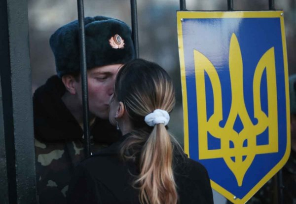 19.) A Ukrainian soldier shares a kiss with his girlfriend, while his base is surrounded by pro-Russian separatists.