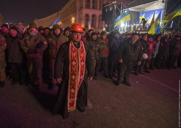 10.) A priest acts as a human shield between protestor and police during protests in Ukraine in 2013.