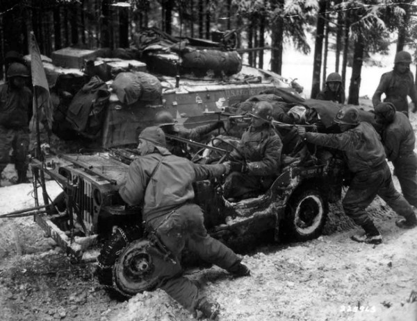 12.) American soldiers push a car carrying two severely wounded German soldiers, 1945.