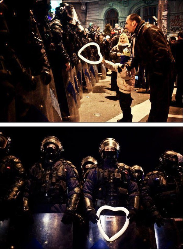 25.) During protests in Romania in 2012, a young boy gives riot police a heart shaped balloon.